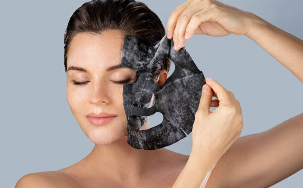 Young woman removing bubble sheet mask from her face on gray background